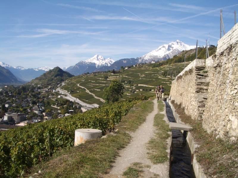 Wanderer entlang der Bisse mit Blick auf das Rhonetal.: Wanderer entlang der Bisse mit Blick auf das Rhonetal.